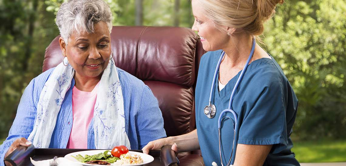 Home care worker serving meal