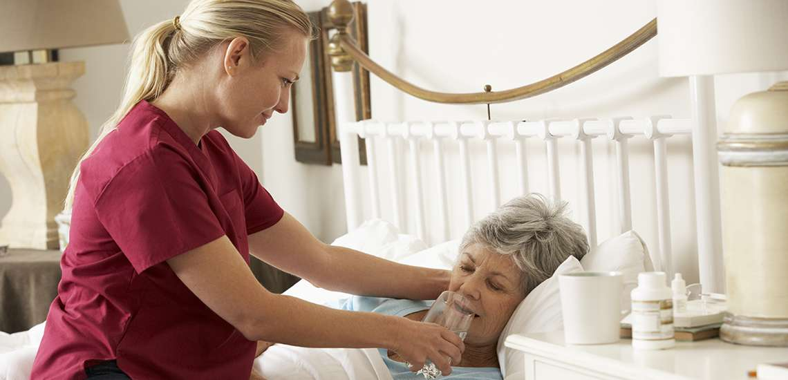 Personal home care worker giving drink of water